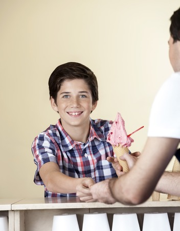 gelati: Portrait of happy boy paying for strawberry ice cream to waiter at counter in parlor Stock Photo