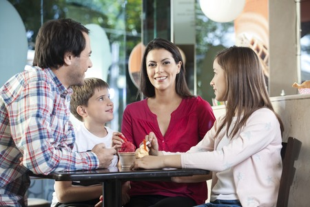 parlor: Smiling family looking at mother sitting at table in ice cream parlor