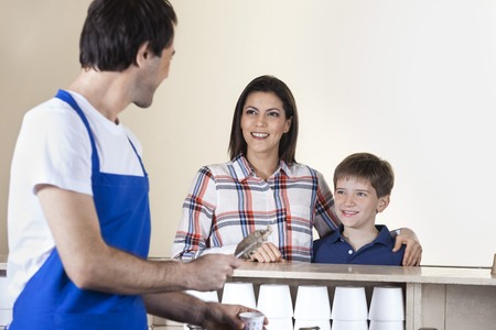 gelati: Waiter serving ice cream to happy family in parlor