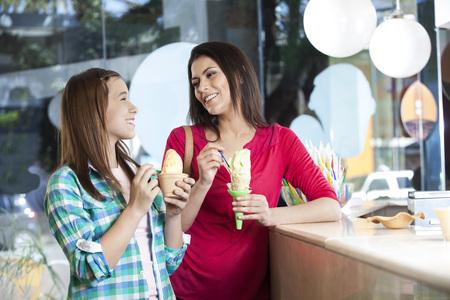 Gelukkige moeder en dochter op zoek naar elkaar onder het genot van ijsjes in de melkstal Stockfoto