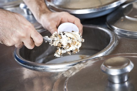 gelati: Closeup of waiters hands filling butterscotch ice cream with spatula in cup at parlor Stock Photo