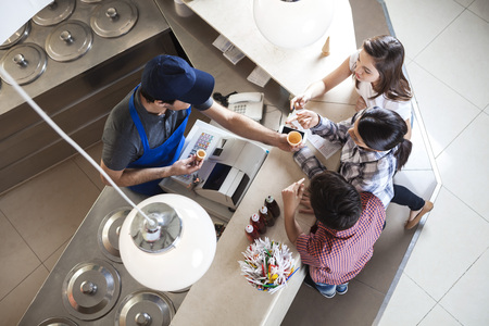 High angle view of family choosing cups at counter in ice cream parlor