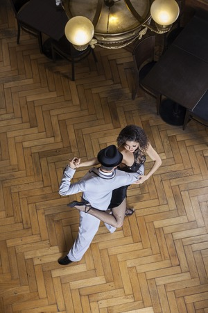 tango: High angle view of confident male and female tango dancers performing on hardwood floor at restaurant