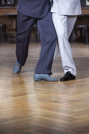 trouser legs: Low section of male tango partners performing scissors step in restaurant