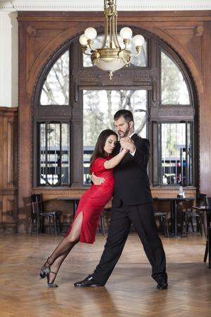 hardwood: Full length of female dancer leaning on partner while performing tango in restaurant Stock Photo