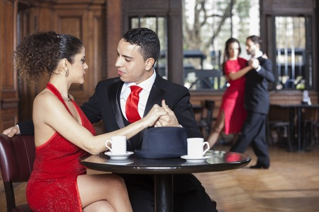 argentina dance: Loving young couple dating while man and woman performing tango in restaurant