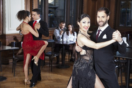 Portrait of confident mid adult man and woman performing tango in restaurant Stock Photo
