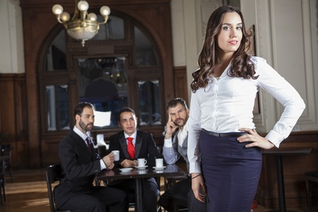 pervert: Portrait of confident tango dancer standing while pervert men looking at her in restaurant Stock Photo
