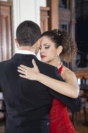 closed club: Beautiful young woman and partner touching foreheads while performing tango in restaurant Stock Photo
