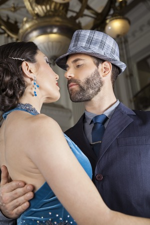 mid adult male: Passionate mid adult male and female dancers performing tango in cafe