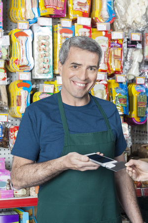 accepting: Portrait of smiling salesman accepting credit card payment from customer in pet store Stock Photo
