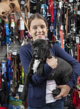petshop: Portrait of smiling girl carrying French Bulldog in pet store