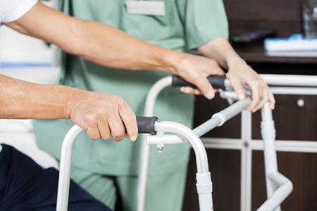 Bebouwd beeld van handen senior mannelijke patiënt met rollator door vrouwelijke verpleegkundige in het revalidatiecentrum