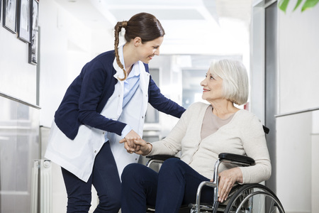 Friendly physiotherapist consoling senior woman sitting in wheelchair at rehab center