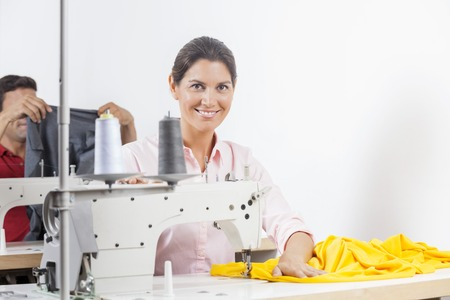 modiste: Portrait of smiling female tailor sitting at working in sewing factory