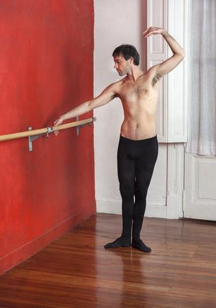 ballet hombres: Longitud total de bailarín de sexo masculino sin camisa practica en la barra de ballet en el estudio de baile