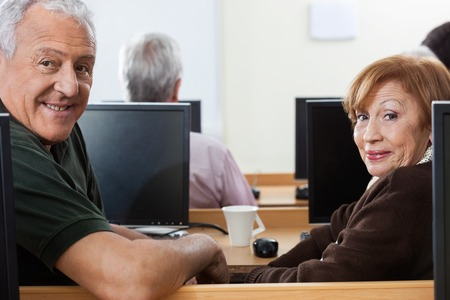 computer classes: Side view portrait of confident senior man and woman sitting at desk in computer class