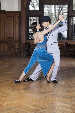 latino dance: Full length of male and female tango dancers performing corte step in restaurant Stock Photo