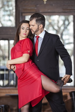 sensuous: Male and female sensuous partners performing high leg wrap in restaurant