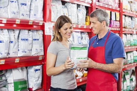 Mature salesman assisting female customer in buying pet food at shop Foto de archivo