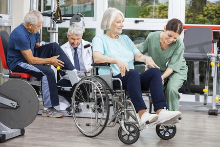 physiotherapists: Disabled senior people being assisted by physiotherapists in rehab fitness center Stock Photo