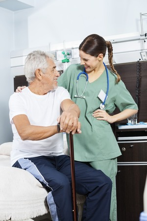 long term care services: Happy senior male patient and young female nurse looking at each other in rehab center
