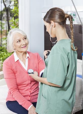 measuring: Female nurse measuring blood pressure of senior woman in rehab center Stock Photo