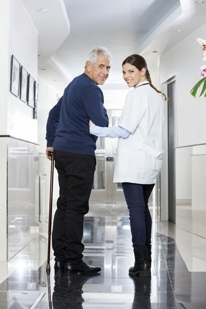 assisted living: Rear view portrait of smiling female doctor walking with senior patient in rehab center Stock Photo
