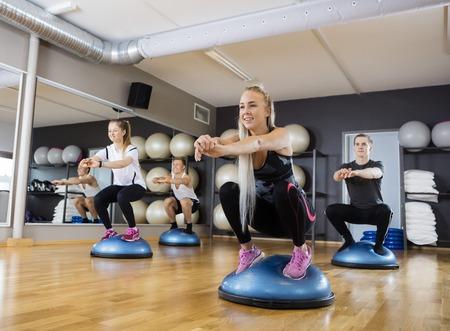 cuclillas: amigos masculinos y femeninos al hacerlo en cuclillas ejercicio en bola del bosu en el gimnasio