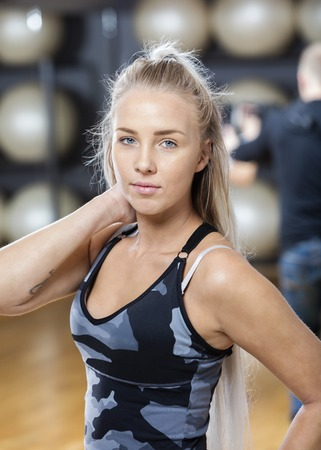 waistup: Portrait of confident young woman touching neck in gym Stock Photo