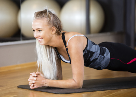 plank: Smiling young woman performing plank exercise in gym