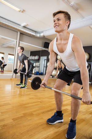 gym class: Smiling young man in sportswear lifting barbell in gym