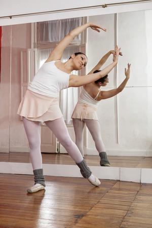reflection mirror: Full length of ballerina performing in training studio
