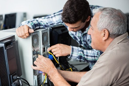 the elderly tutor: Male teacher and senior man fixing computer in classroom