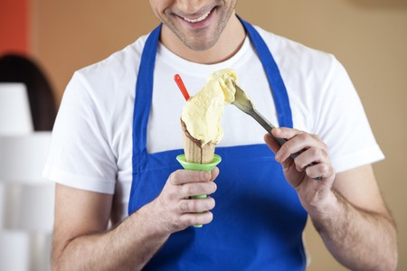 midsection: Midsection of smiling waiter preparing vanilla ice cream in parlor