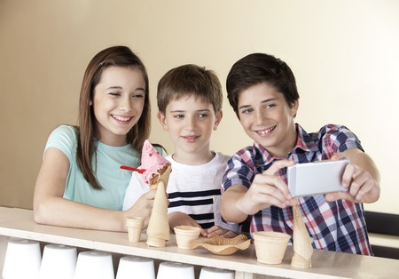 gelati: Happy preteen boy taking selfie with siblings through smart phone at counter in parlor Stock Photo