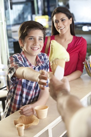 receiving: Happy boy receiving vanilla ice cream cone from seller while standing by mother in parlor Stock Photo