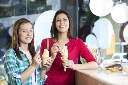parlor: Portrait of smiling mother and daughter with vanilla ice creams in parlor Stock Photo