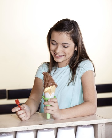 gelati: Happy girl looking at chocolate ice cream at counter in shop