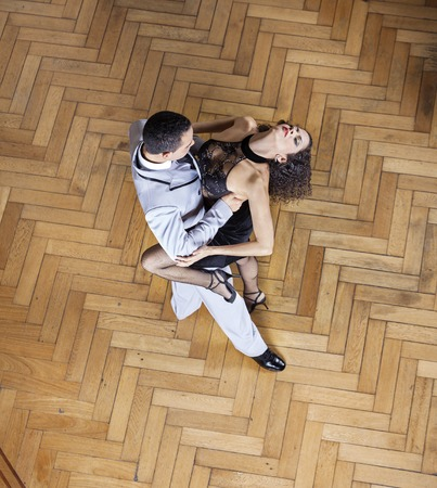 sensuous: High angle view of sensuous young woman and man performing tango on hardwood floor at restaurant Stock Photo