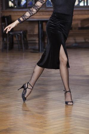 argentina dance: Low section of young woman performing tango on hardwood floor in restaurant