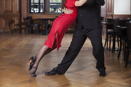 Low section of female dancer leaning on partner while performing tango in restaurant Stock Photo