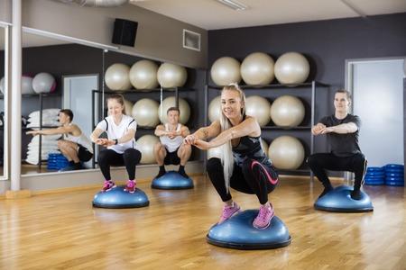 cuclillas: Retrato de mujer joven que hace ejercicio en bola en cuclillas bosu con los amigos en el gimnasio