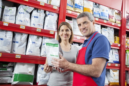 petshop: Portrait of confident salesman assisting smiling customer in buying pet food at shop
