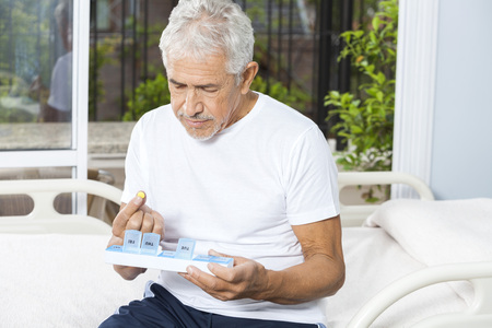 Senior male patient removing pill from container in rehab center