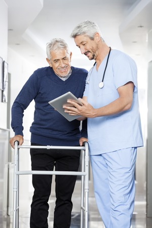 long term care services: Mature physiotherapist showing reports on digital tablet to senior man in rehab center Stock Photo