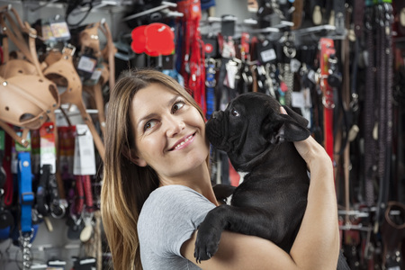 petshop: Smiling mid adult female customer looking away while carrying French Bulldog in store