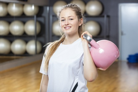 Portrait of attractive woman lifting kettlebell in gym Stock Photo