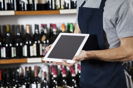 shop keeper: Midsection of salesman showing blank digital tablet in wine shop Stock Photo