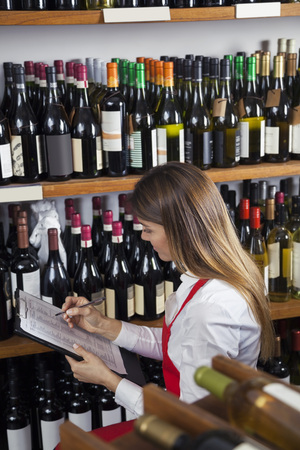 taking inventory: Mid adult saleswoman taking inventory in wine shop